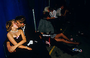 Young adolescent couples kiss and cuddle in a dark corner of a Gatecrashers' Ball in London, England. Three boys and girls dressed in formal evening-wear have been consuming alcohol during the evening and are groping and snogging. The Gatecrasher Ball was an eighties phenomenon conceived by Edward Ormus Sharington Davenport whose parties catered for Public School students. Labled as excessive and out of control events, Davenport charged .£14 a ticket, for often 3,000 kids although he was later fined for tax evasion. .