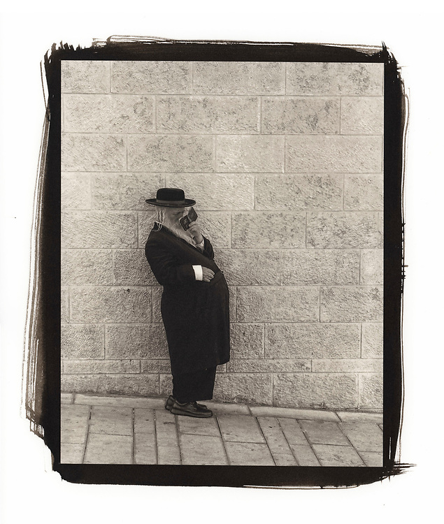 A portrait of a man praying who is standing near the Wailing Wall in Jerusalem.