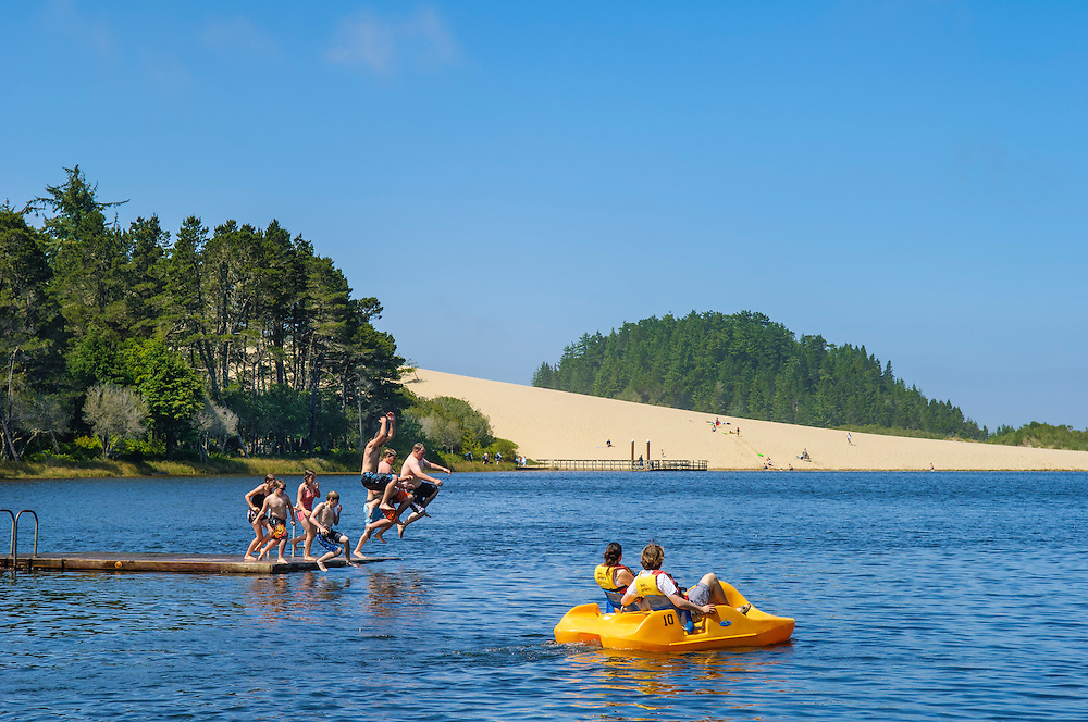 Couple in paddleboat and group of teenagers jumping off float at Cleawox Lake in Honeyman State Park on the Oregon Coast.