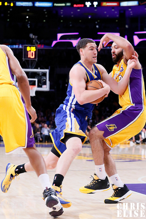 11 April 2014: Golden State Warriors guard Klay Thompson (11) drives past Los Angeles Lakers guard Kendall Marshall (12) during the Golden State Warriors 112-95 victory over the Los Angeles Lakers at the Staples Center, Los Angeles, California, USA.