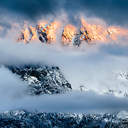 Warm light covers the peaks of the Teton range at sunrise as fog clears in the valley to highlight freshly fallen autumn snow.
