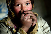 Fatemah, 12, is blowing in her hands to warm up in the early hours of a cold winter morning in the cave where her family resides since seven years, in Bamyan, central Afghanistan, an area mostly populated by Hazaras. A historically persecuted minority (15%) due to more lenient Islamic faith and characteristic 'Eastern' lineaments, Hazaras constitute the 70% of Bamyan's population.