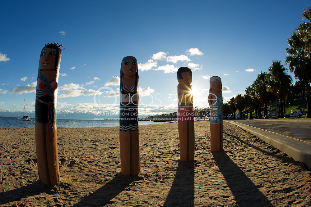 Sunrise behind totem polls decorated/painted as women in bathing suits. Eastern Beach, Geelong, Victoria, Australia. Photo By Lucas Wroe