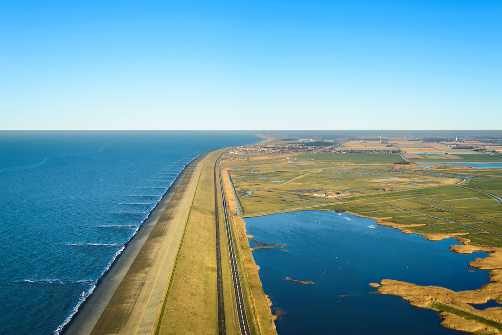 Nederland, Noord-Holland, Gemeente Schoorl, 11-12-2013; Camperduin, Hondsbossche en Pettemer Zeewering gezien naar het noorden, Petten en de duinen aan de horizon. Rechts van de zeedijk de Vereenigde Harger- en Pettemerpolder met 'De Putten' (ontstaan in het verleden door het uitgegraven grond om de  zeewering te verstevigen). De dijk is aangelegd als zeewering nadat de oorsrponkelijke duinen weggeslagen waren. Door erosie kalven de duinen langs de kust steeds verder af, de dijk steekt daardoor steeds meer uit in zee.<br /> Hondsbossche and Pettemer seawall seen to the north, Petten and the dunes on the horizon. Right side of the seawall and the United Harger Pettemer Polder with 'The Wells' (created in the past by using soil for strengthening the seawall). The dike was built as a seawall after the primal dunes were washed away. Because of erosion the dunes decrease in size, therefore the sewall sticks more and more out into the sea.<br /> luchtfoto (toeslag op standard tarieven);<br /> aerial photo (additional fee required);<br /> copyright foto/photo Siebe Swart