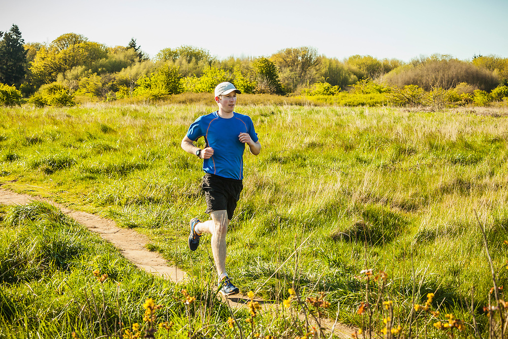 A young man jogging in Discovery Park, Seattle, Washington.