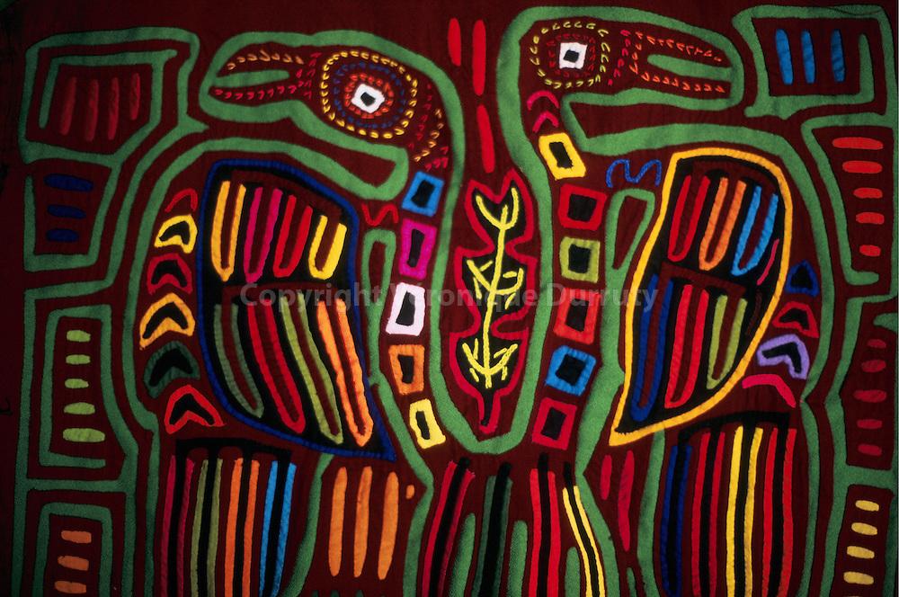 Les molas sont l'art des femmes indigenes kunas. Les premiers temoignages relatifs a la fa?on de s'habiller des kunas datent de la fin du XVIIs siecle. Selon les voyageurs de l epoque, les femmes kuna nouaient un tissu autour de laur taille et couvraient le reste de leur corps de dessins aux motifs divers qu'elles composaient et peignaient elles-meme. ce seraiot ? la faveur de l'introduction du fil a coudre, du cton et des aiguilles que les premieres molas auraient ete confectionnees. Au XIXe siecle, les ecrits rapportent que les femmes arborent des tuniques brodees. L'art des molas serait donc recent, encourage par les rapports des Kunas avec les Blancs. pour ne pas rester torse nu, les femmes auraient remplace leurs peintures corporelles par des dessins sur tissu, en l'occurence des pieces de tissu cousues et superposees selon la technique de l'applique.// The mola is a traditional textile art form made by the Kuna people of Panama and Colombia. Molas are cloth panels, made to wear on clothing, and feature complex designs made with multiple layers of cloth in a reverse appliqu? technique.  Molas are used to decorate the blouses of the Kuna women; although most mola makers are women, a few men take up the art, and some of these are very highly regarded. Molas are still made by Kuna women for their own use; however, sale of molas to tourists and craft centres is a major source of income for the Kuna people.