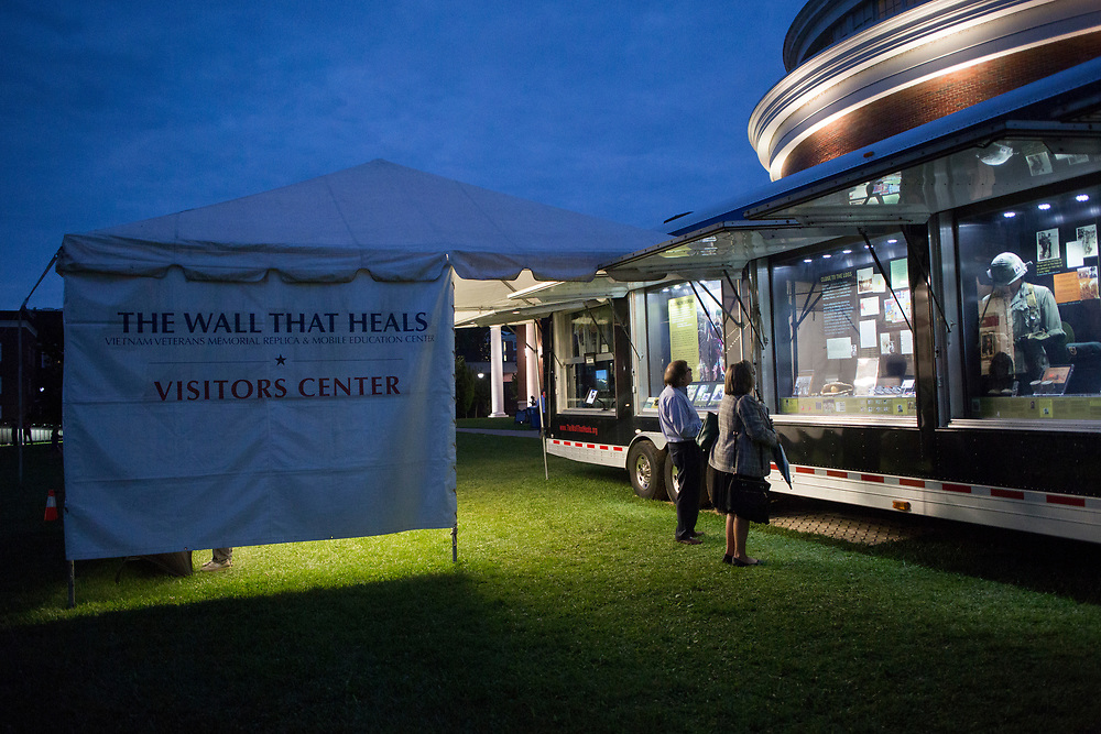 """Visitors looks at exhibits of photos, letters, and memorabilia from the Vietnam War as part of """"The Wall That Heals"""", display in Bicentennial Park on September 15, 2017."""