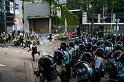 A policeman throws a flare at protesters occupying roads in front of the Central Government Offices, during a protest against a proposed extradition law in Hong Kong, SAR China, on Wednesday, June 12, 2019. Hong Kong's legislative chief postponed the debate on legislation that would allow extraditions to China after thousands of protesters converged outside the chamber demanding the government to withdraw the bill. Photo by Suzanne Lee/PANOS