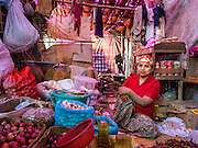 09 NOVEMBER 2014 - SITTWE, RAKHINE, MYANMAR: A Rohingya Muslim woman shopkeeper in a market in a Rohingya Muslim IDP camp near Sittwe. After sectarian violence devastated Rohingya communities and left hundreds of Rohingya dead in 2012, the government of Myanmar forced more than 140,000 Rohingya Muslims who used to live in and around Sittwe, Myanmar, into squalid Internal Displaced Persons camps. The government says the Rohingya are not Burmese citizens, that they are illegal immigrants from Bangladesh. The Bangladesh government says the Rohingya are Burmese and the Rohingya insist that they have lived in Burma for generations. The camps are about 20 minutes from Sittwe but the Rohingya who live in the camps are not allowed to leave without government permission. They are not allowed to work outside the camps, they are not allowed to go to Sittwe to use the hospital, go to school or do business. The camps have no electricity. Water is delivered through community wells. There are small schools funded by NOGs in the camps and a few private clinics but medical care is costly and not reliable.  PHOTO BY JACK KURTZ