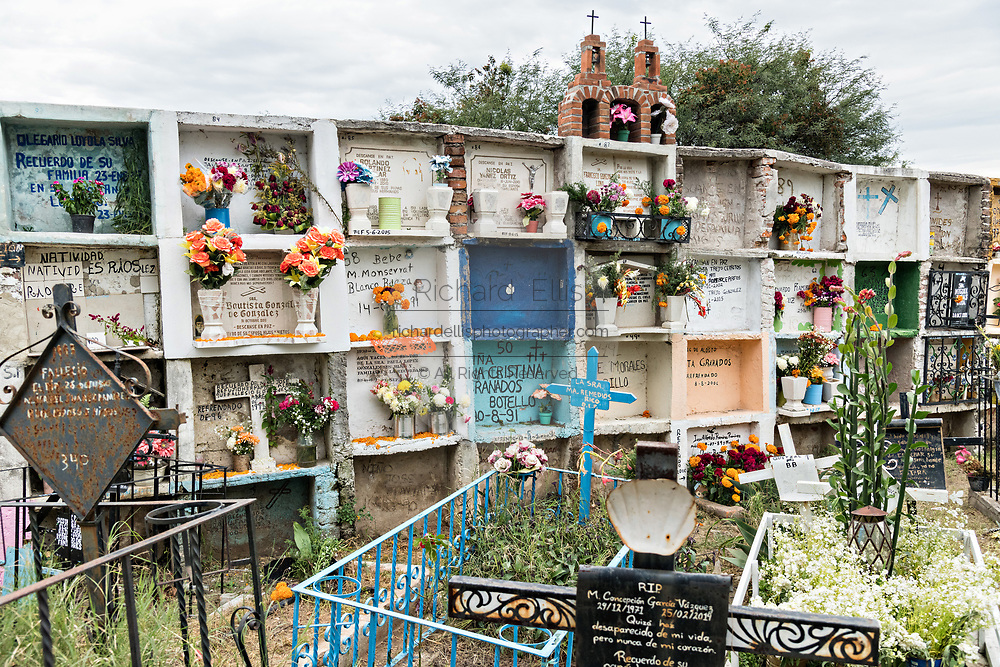 Decorated cremation niches at the Our Lady of Guadalupe cemetery during the Dead of the Dead or Dia de Muertos festival in San Miguel de Allende, Mexico. The multi-day festival is to remember friends and family members who have died using calaveras, aztec marigolds, alfeniques, papel picado and the favorite foods and beverages of the departed.