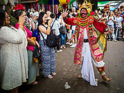 "02 AUGUST 2017 - UBUD, BALI, INDONESIA: A traditional Balinese dancer performs in front of the temple during the ""Merchants' Day"" ceremony at the Pura (Temple) Melanting Pasar Ubud, the small Hindu temple in the Ubud market. It's a day that merchants throughout Ubud come to the temple to make offerings and pray for prosperity.    PHOTO BY JACK KURTZ"