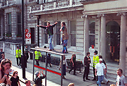 Ravers on top of bus stop, 1st Criminal Justice March, London, UK, 1st of May 1994.