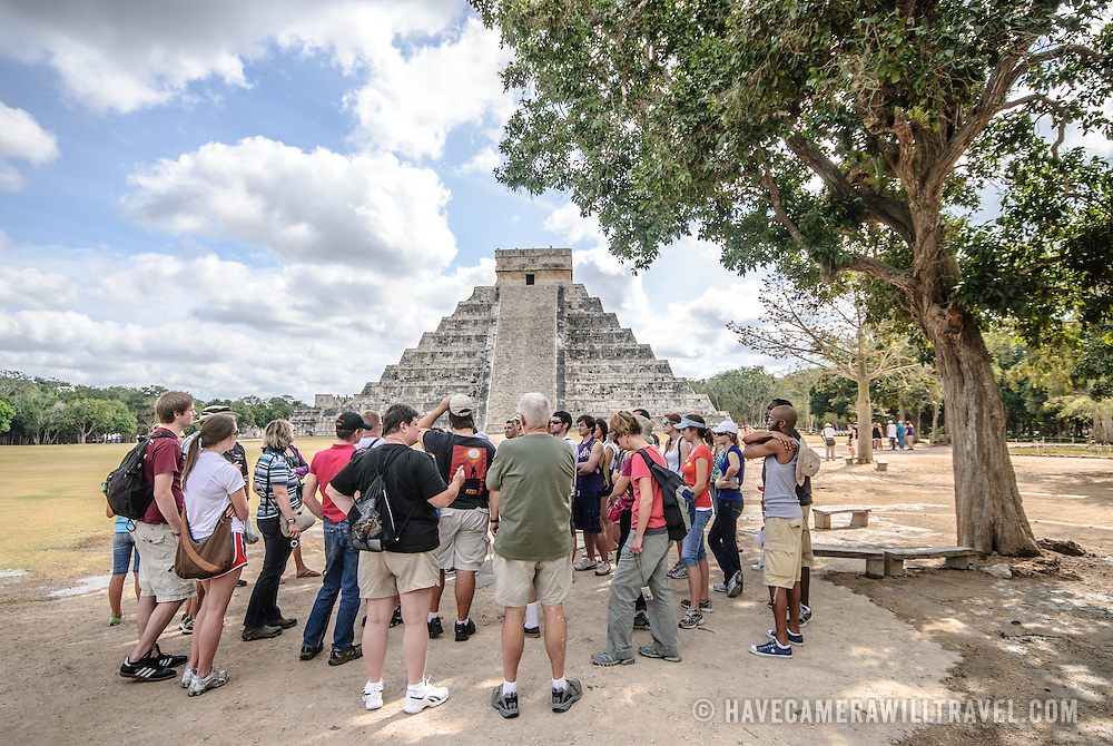 Visitors standing in front of the Temple of Kukulkan (El Castillo) at Chichen Itza Archeological Zone, ruins of a major Maya civilization city in the heart of Mexico's Yucatan Peninsula.