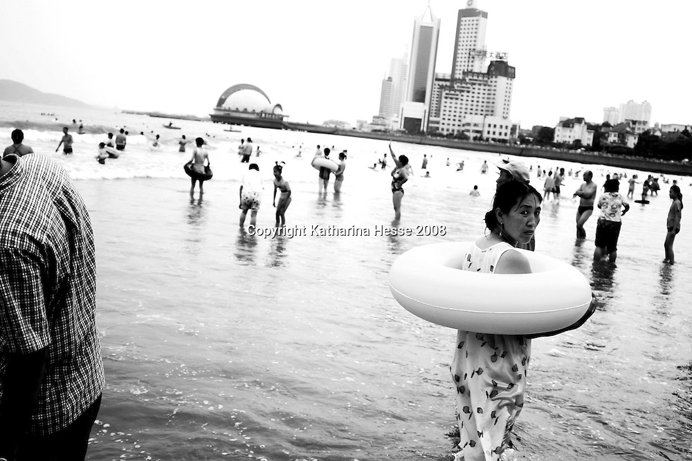 QINGDAO, AUGUST-17,2003:  a woman with a swiming belt by the beach. Many Chinese adults never learnt to swim, therefore the swimming belts.