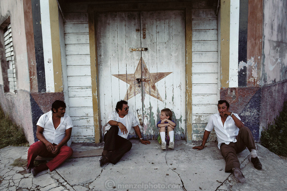 Evan Menzel, a young American tourist, talking to taxi drivers who are taking a break. Maya ruins trip. Corozal, Belize.  Central America.