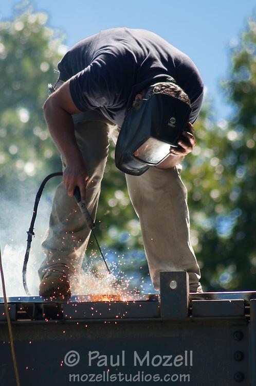 Ironworker welds steel girders on building in Wakefield, MA