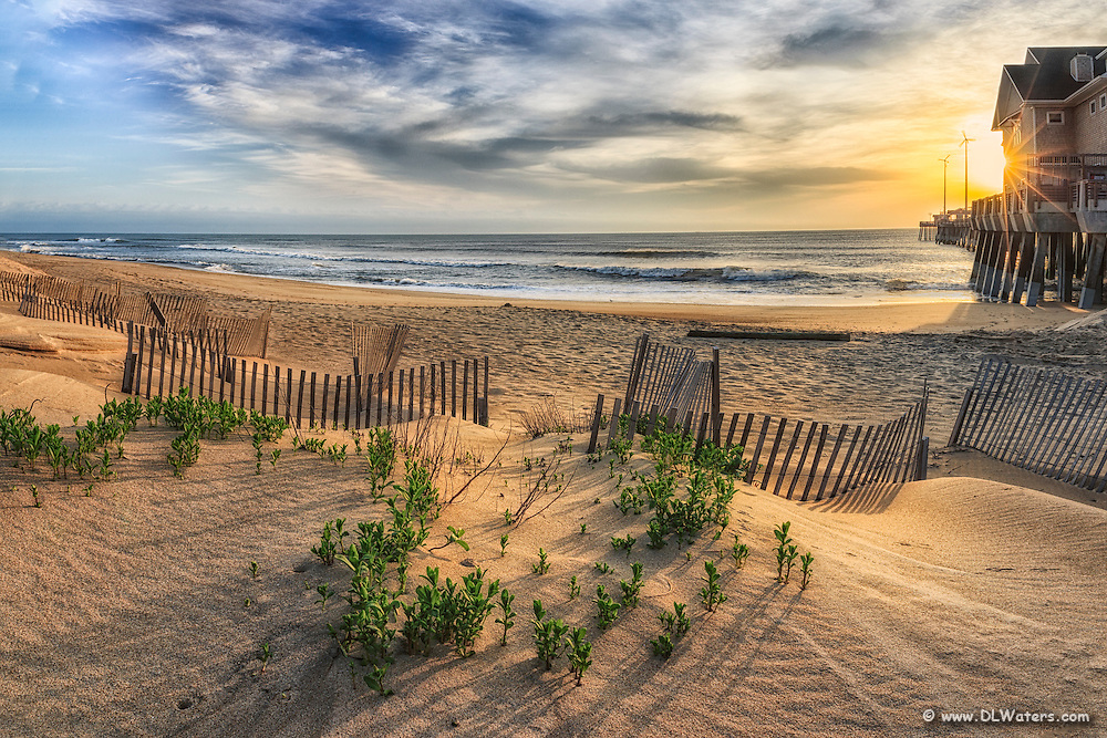 Sand dune and sand fence at sunrise next to  Jennette's Pier in Nags Head on the Outer Banks of NC.