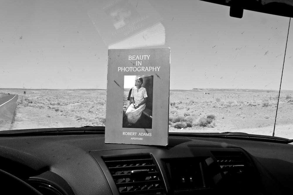 The Book BEAUTY IN PHOTOGRAPHY by Robert Adams is standing on the black dashboard of a car. Photo taken in Arizona; USA.