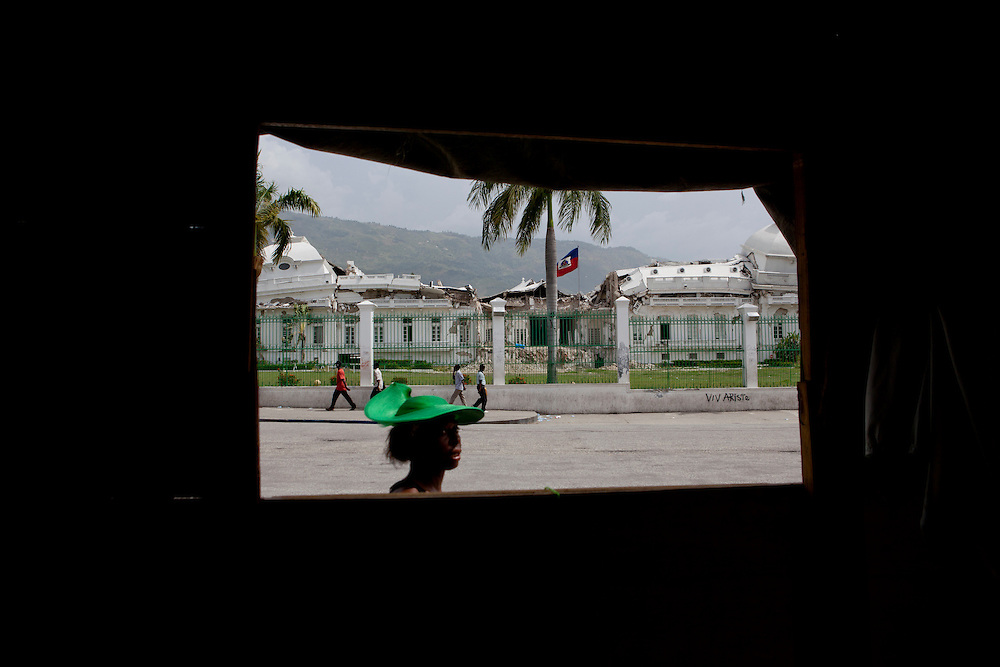 PORT-AU-PRINCE, HAITI - JULY 12: A woman passes by the window of a shack with a view of the destroyed National Palace on July 12, 2010 in Port-au-Prince, Haiti. Six months after an earthquake killed an estimated 230,000 people, many Haitians are struggling to rebuild their lives. (Photo by Brendan Hoffman/Getty Images) *** Local Caption ***