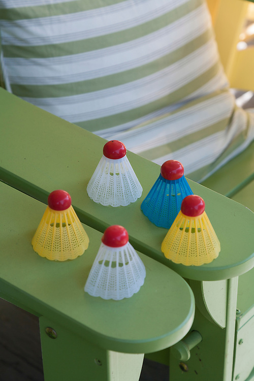 Colorful badminton birdies sit on green adirondack chair arm with striped cushion