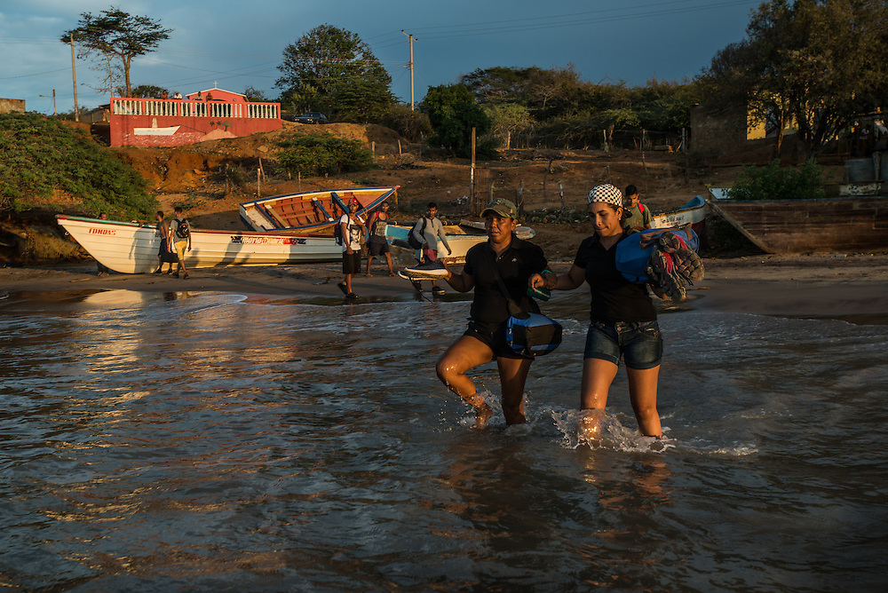 FALCÓN, VENEZUELA - SEPTEMBER 26, 2016: Maria Piñero and Andrea Gomez, both undocumented migrants, walk into the water to board a smuggler's boat that will illegally take them from Venezuela to Curaçao. Undocumented migrants here have mortgaged property, sold kitchen appliances and even borrowed money from the same smuggling rings that pack them on the floorboards alongside drugs and other contraband. The journey to Curaçao takes them on a 60-mile crossing filled with backbreaking swells, gangs of armed boatmen and coast guard vessels looking to capture migrants and send them home. Then, after being tossed overboard and left to swim ashore, they hide in the brush to meet contacts who spirit them anew into the tourist economy of this Caribbean island. They clean the floors of restaurants, work in construction, sell trinkets on the street, or even solicit Dutch tourists for sex. But at least, the migrants say, there is food. PHOTO: Meridith Kohut for The New York Times
