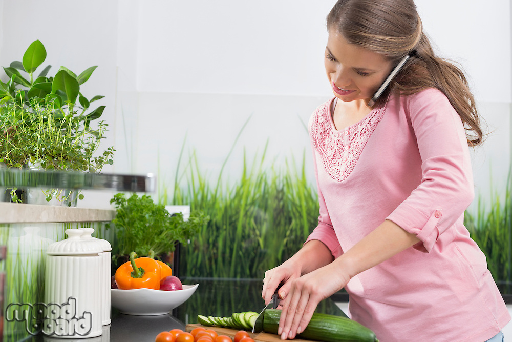 Woman using cell phone while cutting cucumber at kitchen counter
