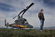 Mountain West Helicopter Pilot Tim Norton poses for a portrait next to a Kaman K-MAX 1200 twin rotor helicopter Thursday, April 5, 2012 at Vance Brand Municipal Airport in Longmont. The K-MAX is capable of lifting up to 6000 lbs of cargo including water for fire fighting, seed or ski lift equipment. Next week, Norton will be flying a rehab mission over Sunshine Canyon to help reseed the area..(Matthew Jonas/Times-Call)