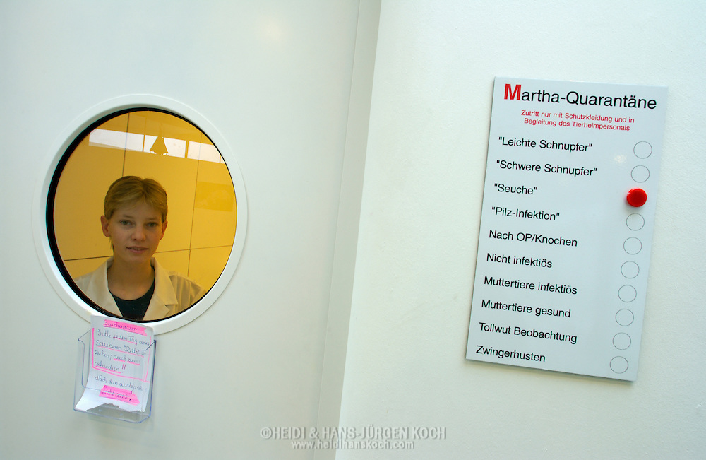 "Deutschland, DEU, Berlin, 2003: die Arzthelferin Katja Keller in einer Quarantaenestation der Tierklinik. Rechts haengt eine Pinwand, die anzeigt, welche Art von Infektion sich hinter der Tuer befindet. In diesem Fall ist das Feld ""Seuche"" markiert. Das Berliner Tierheim ist das groesste und modernste auf der Welt. 