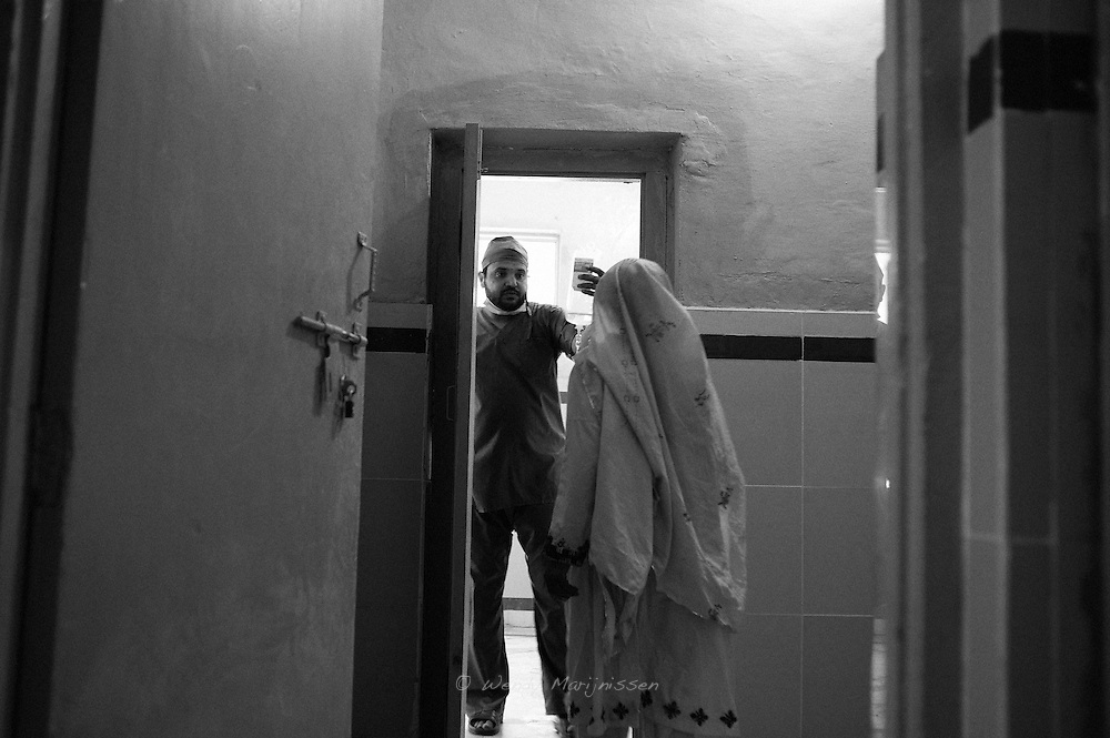 A doctor is leading a woman into the operating theatre during a surgical camp in the local village medical centre. Free of charge, the surgery will be provided to women who could not afford this necessary medical care and would continue suffering for years with conditions like a prolapsed utures. Jafferabad, Pakistan, 2010