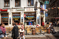 Photo of people enjoying a beautiful day at a corner bar in Brussels, Belgium.