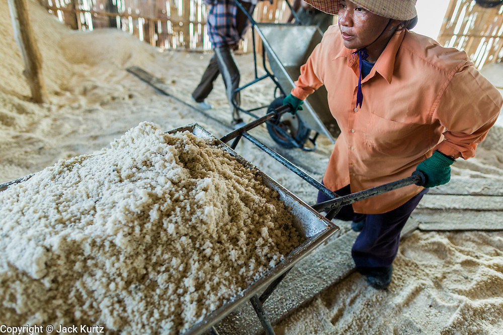 """28 MARCH 2014 - NA KHOK, SAMUT SAKHON, THAILAND:  Thai workers stack salt in a warehouse in Samut Sakhon province.Thai salt farmers south of Bangkok are experiencing a better than usual year this year because of the drought gripping Thailand. Some salt farmers say they could get an extra month of salt collection out of their fields because it has rained so little through the current dry season. Salt is normally collected from late February through May. Fields are flooded with sea water and salt is collected as the water evaporates. Last year, the salt season was shortened by more than a month because of unseasonable rains. The Thai government has warned farmers and consumers that 2014 may be a record dry year because an expected """"El Nino"""" weather pattern will block rain in mainland Southeast Asia. Salt has traditionally been harvested in tidal basins along the coast southwest of Bangkok but industrial development in the area has reduced the amount of land available for commercial salt production and now salt is mainly harvested in a small parts of Samut Songkhram and Samut Sakhon provinces.   PHOTO BY JACK KURTZ"""