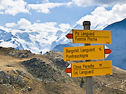 "A sign marks trails above Pontresina with good views of Piz Palü (3901 meters or 12,799  feet) and the Bernina massif, in Upper Engadine, Grison Alps, Switzerland, Europe. The Swiss valley of Engadine translates as the ""garden of the En (or Inn) River"" (Engadin in German, Engiadina in Romansh, Engadina in Italian)."