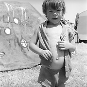 A young boy has his name written on his chest in biro detailing his name, location, and the registration of his parents vehicle, Glastonbury, Somerset, 1989