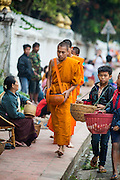 "11 MARCH 2013 - LUANG PRABANG, LAOS:  A Buddhist monk walks through the streets of Luang Prabang during the tak bat. The ""Tak Bat"" is a daily ritual in most of Laos (and other Theravada Buddhist countries like Thailand and Cambodia). Monks leave their temples at dawn and walk silently through the streets and people put rice and other foodstuffs into their alms bowls. Luang Prabang, in northern Laos, is particularly well known for the morning ""tak bat"" because of the large number temples and monks in the city. Most mornings hundreds of monks go out to collect alms from people.   PHOTO BY JACK KURTZ"