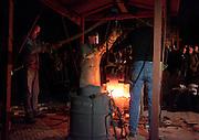 Klokkengieter Simon Laudy (midden) haalt de bak met brons van 1100 graden uit de speciaal gemaakte oven. Op de Domplein in Utrecht wordt een klok gegoten dat door de Utrechtse Klokkenluidersgilde wordt geschonken aan het  Academiegebouw van de Universiteit Utrecht ter gelegenheid van hun 375 jarig bestaan in 2011. Het is voor het eerst sinds eeuwen dat weer een klok in het openbaar wordt gegoten. De klok gaat Anna Maria (genoemd naar de eerste vrouwelijke student aan de universiteit, Anna Maria van Schurman) heten en is gemaakt van brons.<br /> <br /> Bell-founder Simon Laudy (center) is taking the hot bronze out of the oven. For the first time in centuries a bell is being casted publicly at the Domplein in Utrecht. The 100 kg bronze bell is a present of the Utrecht Bell-ringing Guild to the University Utrecht which is celibrating its 375 year's anniversary in 2011. The bell is named Anna Maria after the first female student of the university.