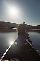 Young woman canoeing on a lake in fall. Arrowhead Provincial Park, Muskoka, Ontario, Canada.
