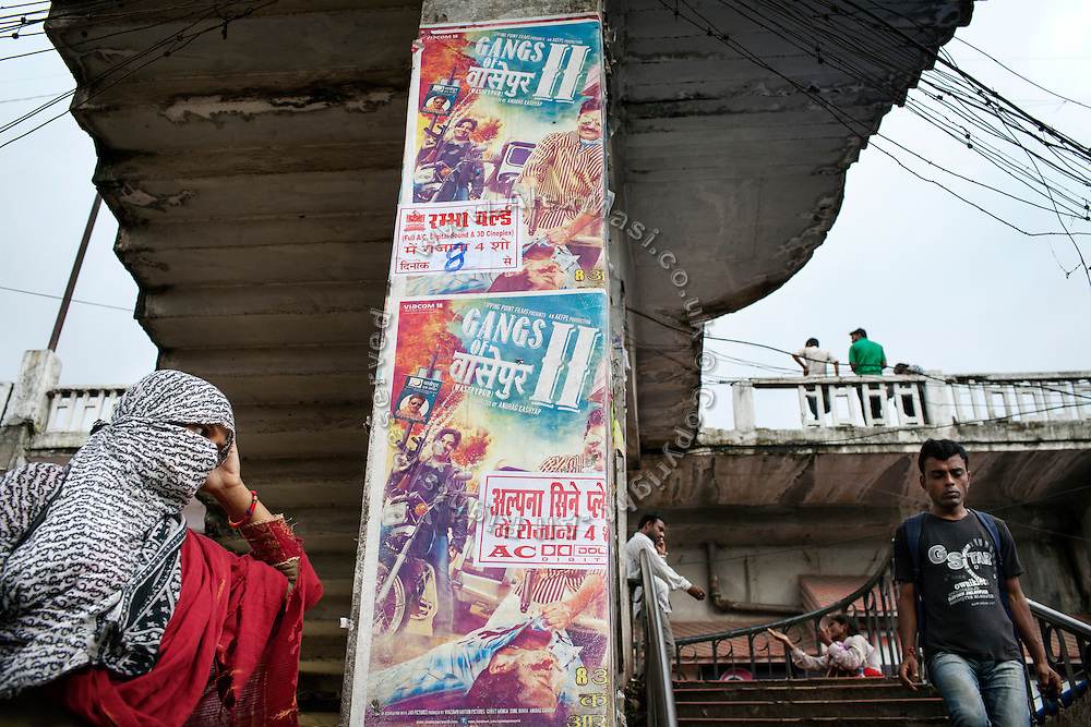 A woman is walking next to Bollywood movie posters of the film 'Gangs of Wasseypur II', affixed on a pedestrian crossing over a  junction in Bhopal, Madhya Pradesh, India.