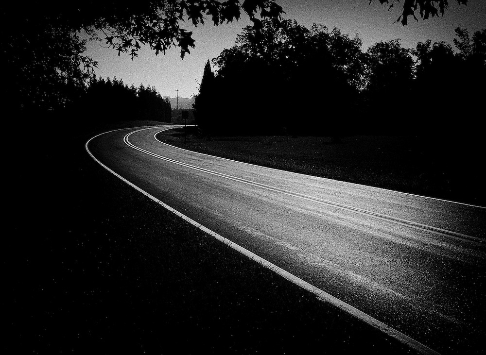Dark black and white image of a winding road  and trees in North Carolina.