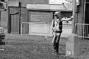 Man wearing horse mask and leather clothes, leaning against a lamppost. Trash City. Glastonbury 2009