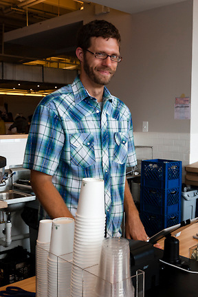 Ryan, the owner of Peregrine Expresso, a Capitol Hill institution, smiles behind the counter of his new operation in the Union Market.