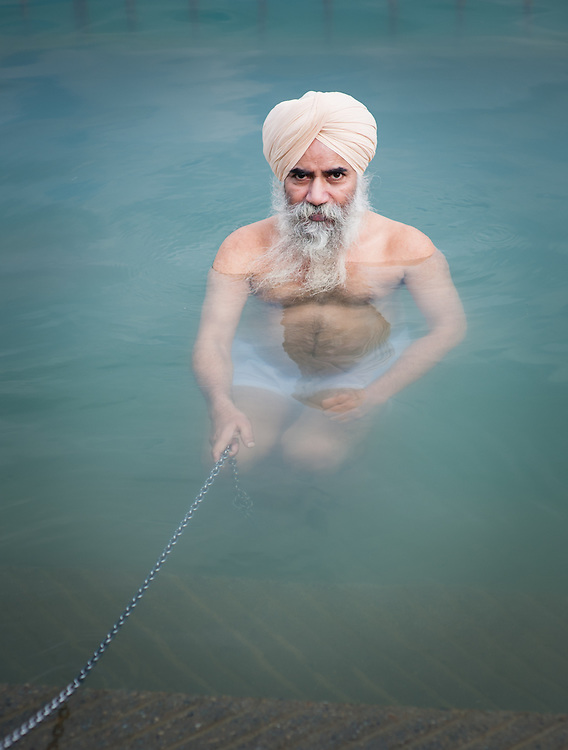 Sikh man with white turban bathing at Golden Temple pool in Amritsar (India)