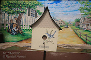 Fanciful painted birdhouse blends with mural in author Harper Lee's hometown depicting Scout, Jem and Dill hiding behind tree to spy on Boo Radley in scene from To Kill a Mockingbird; Monroeville, Alabama.