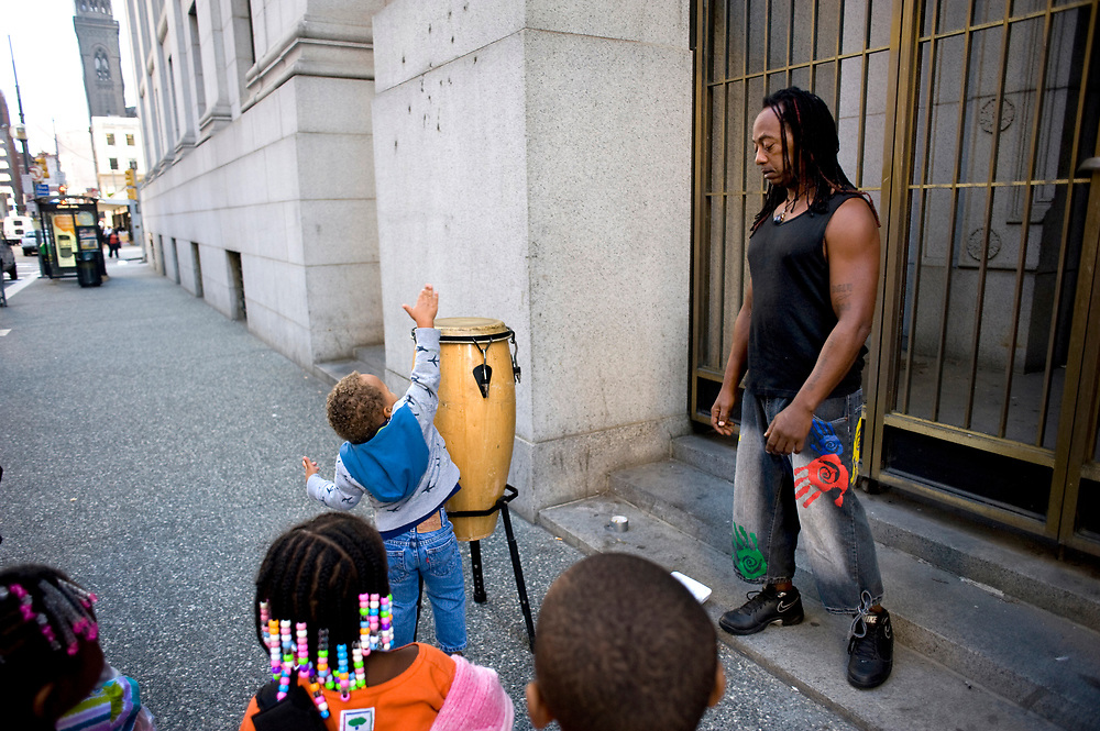 Drummer Price Bennett (right) watches as Josiah Hartley, age 4, from Small World 2 Early Learning & Development Center, tries to reach the top of his drum on Smithfield Street in downtown Pittsburgh. The preschoolers take regular walks through downtown Pittsburgh.