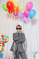Young boy wearing sunglasses and standing with arms crossed holding party balloons