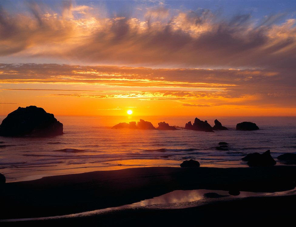 A wildly-colored sunset graces the sky at Face Rock Wayside on the Oregon Coast. ©Ric Ergenbright