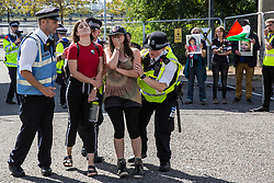 London, UK. 2 September, 2019. Metropolitan Police officers remove pro-Palestinian activists blocking the road in front of a HGV delivering to ExCel London on the first day of week-long protests against DSEI 2019, the world's largest arms fair.