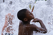 Unidentified boy cooling off  in the Fountain of Rings located in  Centennial Olympic Park, downtown Atlanta,  Georgia August 9, 2013