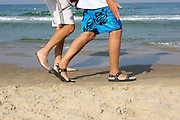 The feet of two young men walking on the beach, Tel Aviv Israel October 2005