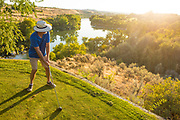 Senior man teeing off while backlit on the 14th tee at Clear Lakes Country Club in Buhl, Idaho. MR