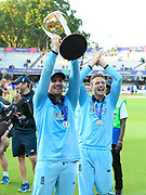 Jason Roy of England holds up the Cricket World Cup trophy on the lap of honour with Jos Buttler of England clapping during the ICC Cricket World Cup 2019 Final match between New Zealand and England at Lord's Cricket Ground, St John's Wood, United Kingdom on 14 July 2019.